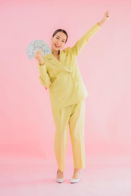 Retrato de uma bela jovem asiática de negócios com muito dinheiro ou dinheiro em cores Foto gratuita