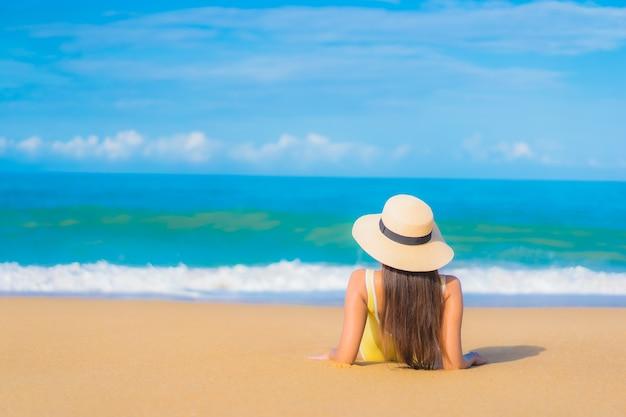 Retrato de uma bela jovem asiática relaxando na praia em viagens de férias Foto gratuita