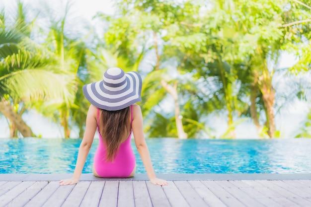 Retrato de uma bela jovem asiática sorrindo relaxando ao redor da piscina em um hotel resort em uma viagem de férias de férias Foto gratuita