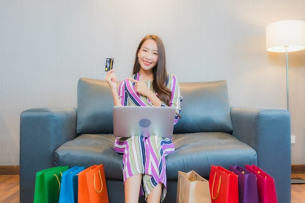 Retrato de uma bela jovem asiática usando computador, laptop ou telefone celular inteligente com cartão de crédito para fazer compras online Foto gratuita