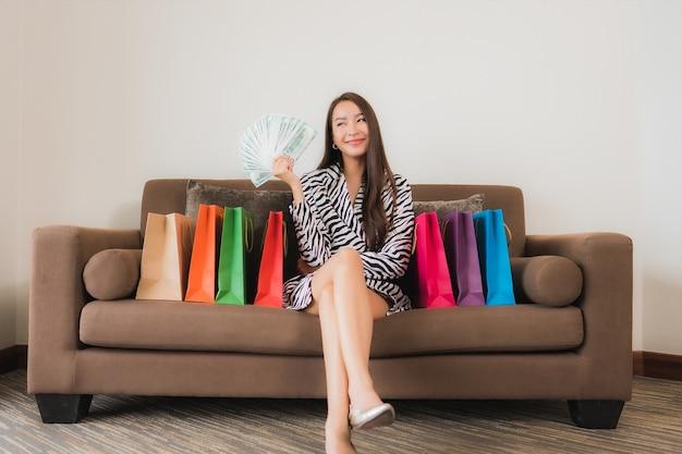 Retrato de uma bela jovem asiática usando laptop, celular inteligente ou dinheiro para fazer compras online no sofá no interior da sala de estar Foto gratuita