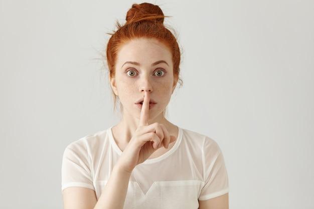 Retrato de uma bela jovem caucasiana com coque ruivo segurando o dedo indicador nos lábios Foto gratuita