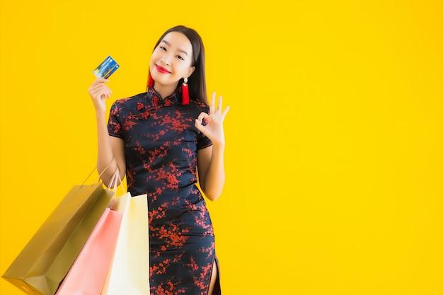 Retrato de uma bela jovem mulher asiática usa vestido chinês com sacola de compras Foto gratuita