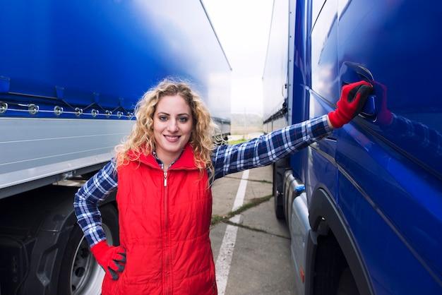 Retrato de uma caminhoneira parada perto de um caminhão Foto gratuita