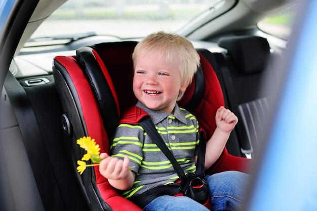 Retrato de uma criança nova de um menino com cabelo louro em um banco de carro das crianças. Foto Premium