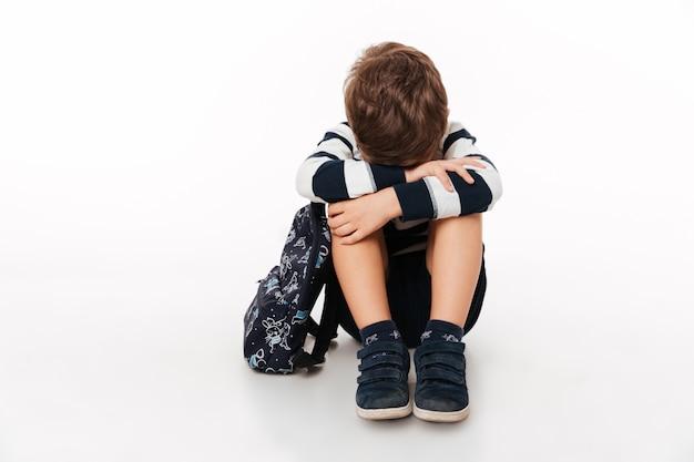 Retrato de uma criança triste chateada com mochila Foto gratuita