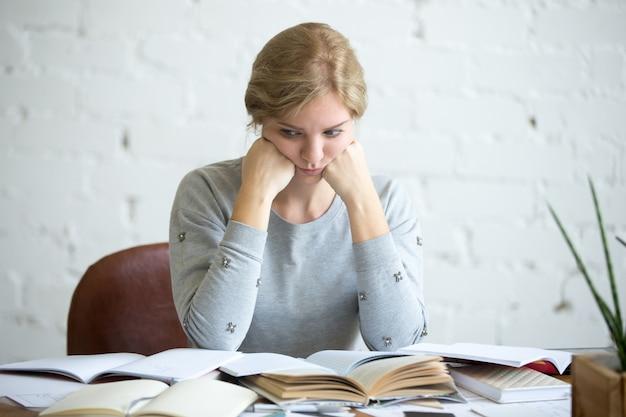 Retrato de uma estudante cansada na mesa Foto gratuita