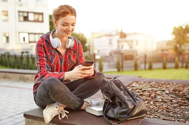 Retrato de uma estudante fêmea do ruivo novo em uma camisa quadriculado. Foto Premium