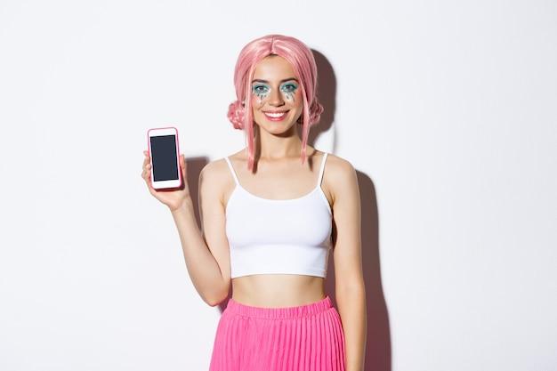 Retrato de uma festeira sorridente com peruca rosa, mostrando a tela do smartphone e parecendo satisfeita, recomenda algo, em pé. Foto gratuita