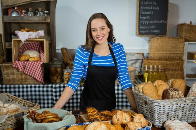 Retrato de uma funcionária sorridente em pé no balcão de pão Foto Premium