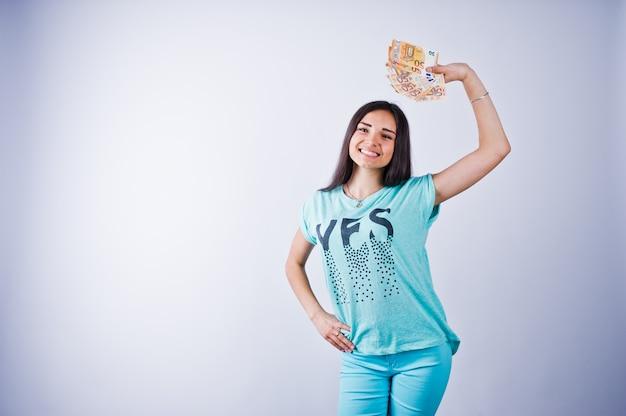 Retrato de uma garota atraente em camiseta azul ou turquesa e calça posando com muito dinheiro na mão. Foto Premium