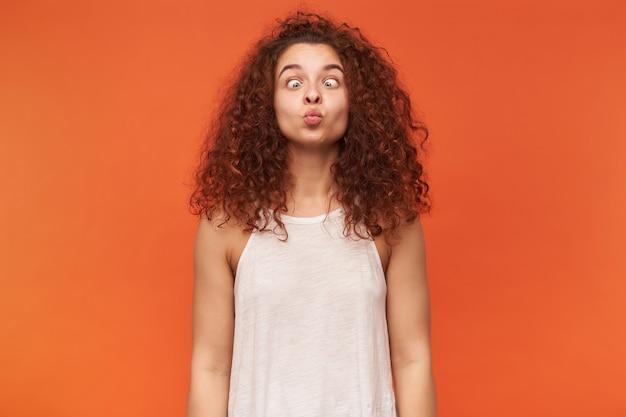 Retrato de uma garota ruiva adulta, engraçada, com cabelo encaracolado. usando uma blusa branca sem ombros. apertando os olhos e fazendo cara de boba. isolado sobre a parede laranja Foto gratuita