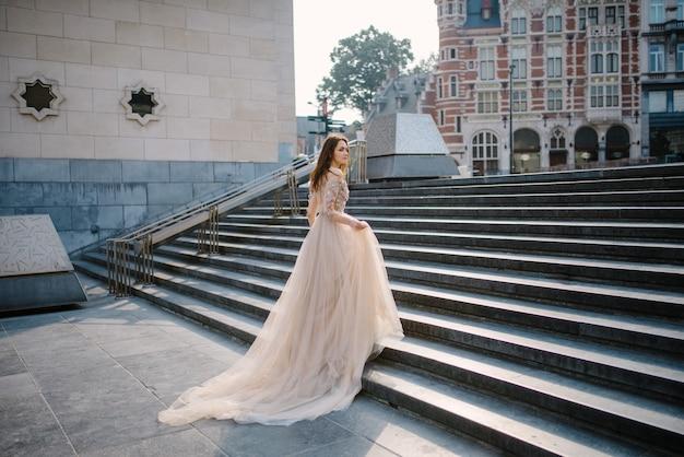 Retrato de uma jovem adorável em um vestido exuberante andando pelo parque e o grande palácio (bruxelas) Foto Premium