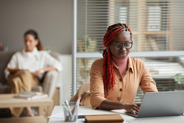 Retrato de uma jovem afro-americana usando laptop enquanto está sentado na mesa no escritório com pessoas no fundo, copie o espaço Foto Premium
