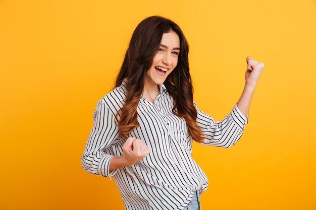 Retrato de uma jovem alegre, comemorando o sucesso Foto gratuita