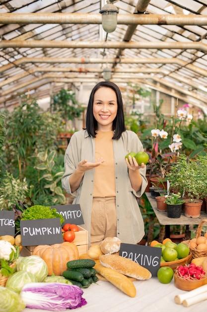 Retrato de uma jovem asiática sorridente com uma camisa falando sobre maçãs frescas no mercado do agricultor Foto Premium