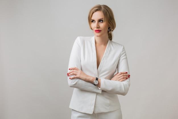 Retrato de uma jovem atraente de terno branco, sexy e confiante, mulher de negócios independente, estilo elegante, lábios vermelhos, expressão séria do rosto, olhar para a câmera, braços cruzados, sorriso Foto gratuita