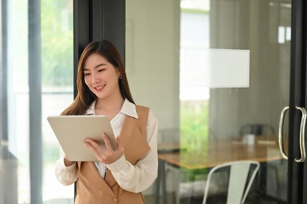 Retrato de uma jovem atraente segurando seu tablet digital enquanto trabalhava em um escritório moderno. Foto Premium