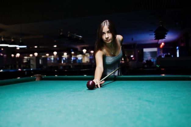 Retrato de uma jovem atraente vestido jogando sinuca. Foto Premium