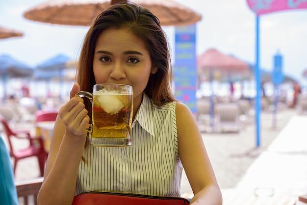 Retrato de uma jovem bela turista asiática sentada em um restaurante na praia ao ar livre Foto Premium
