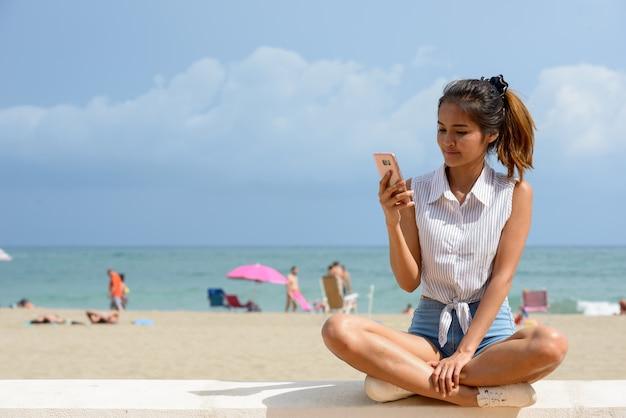 Retrato de uma jovem bela turista asiática sentada na praia ao ar livre Foto Premium
