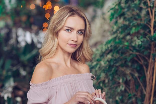Retrato de uma jovem bonita contra plantas turva Foto gratuita