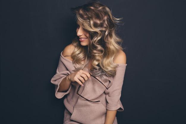 Retrato de uma jovem bonita de cabelos loiro, vestindo óculos da moda e roupas casuais e posando sobre fundo preto Foto gratuita
