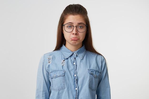 Retrato de uma jovem de óculos com cabelo comprido, vestida com uma camisa jeans Foto gratuita