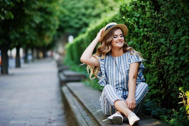 Retrato de uma jovem deslumbrante em macacão listrado sentado no parque. Foto Premium