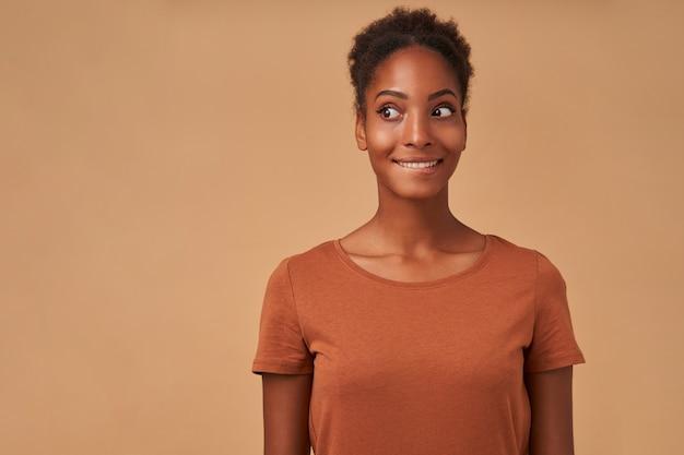 Retrato de uma jovem e adorável morena de pele escura animada mordendo com alegria o lábio inferior enquanto olha alegremente para o lado, isolado no bege Foto gratuita