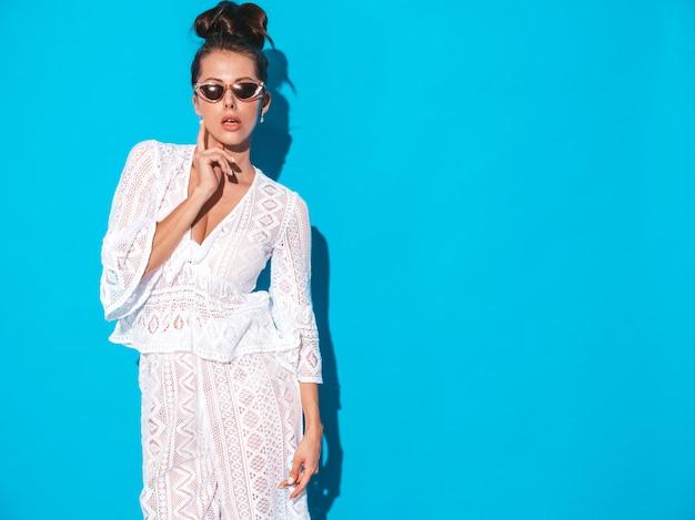 Retrato de uma jovem e bela mulher sexy com penteado ghoul. menina na moda hipster casual verão branco terno roupas em óculos de sol. modelo quente isolado em azul Foto gratuita