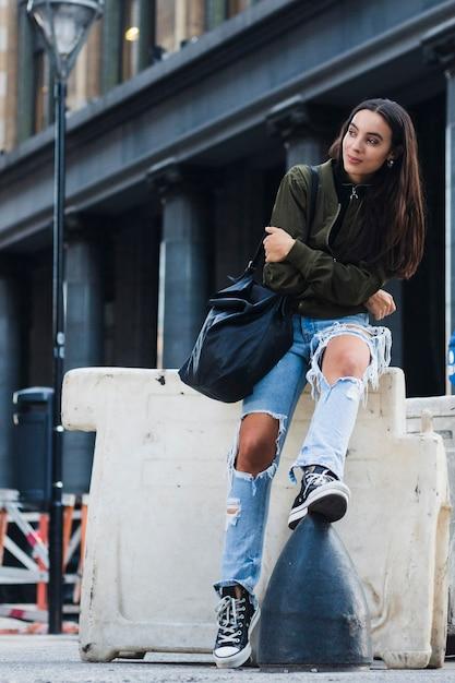 Retrato de uma jovem elegante com saco sentado na rua Foto gratuita