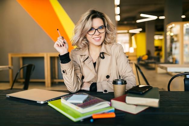 Retrato de uma jovem elegante, tendo uma idéia, sentado à mesa no casaco trabalhando no laptop no escritório colaborador, usando óculos, sorrindo, feliz, positivo, ocupado Foto gratuita