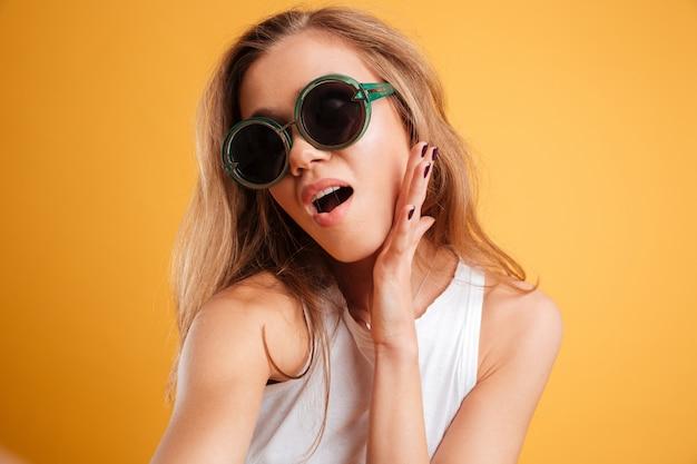 Retrato de uma jovem em óculos de sol, tomando uma selfie Foto gratuita