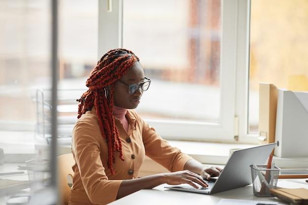Retrato de uma jovem empresária afro-americana usando laptop enquanto está sentado na mesa perto da janela e aproveitando o trabalho no escritório, copie o espaço Foto Premium