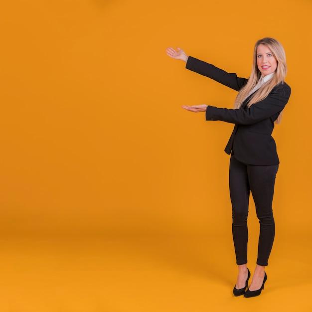 Retrato de uma jovem empresária dando apresentação contra um fundo laranja Foto gratuita