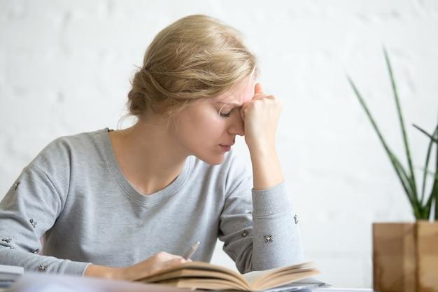 Retrato de uma jovem estudante sobrecarregada de trabalho sentado à mesa Foto gratuita