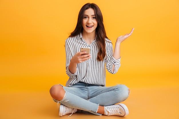 Retrato de uma jovem excitada segurando o telefone móvel Foto gratuita