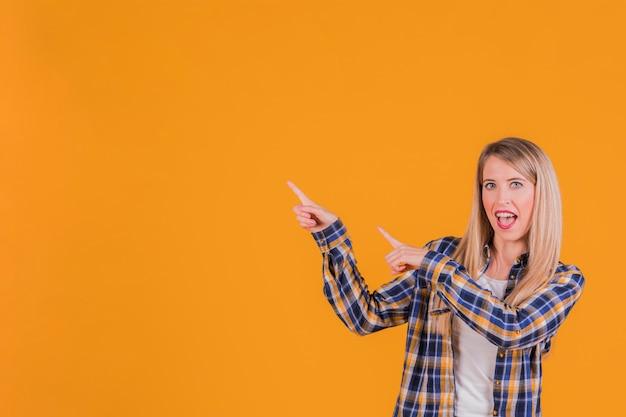 Retrato de uma jovem feliz, apontando os dedos contra um fundo laranja Foto gratuita