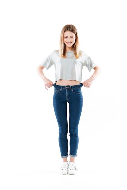 Retrato de uma jovem feliz e feliz em pé e mostrando sua perda de peso isolada Foto gratuita