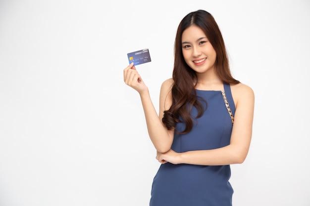 Retrato de uma jovem feliz, segurando o atm ou cartão de débito ou crédito e usando para compras on-line, gastando muito dinheiro isolado, modelo feminino asiático Foto Premium