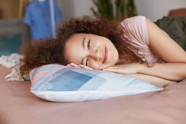 Retrato de uma jovem garota afro-americana alegre deitada na cama, desfrutar da manhã ensolarada em casa, sorrindo e parece feliz. Foto gratuita