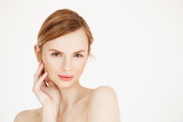 Retrato de uma jovem garota bonita nua sorrindo rosto comovente. tratamento facial. cosmetologia de beleza e spa. Foto gratuita