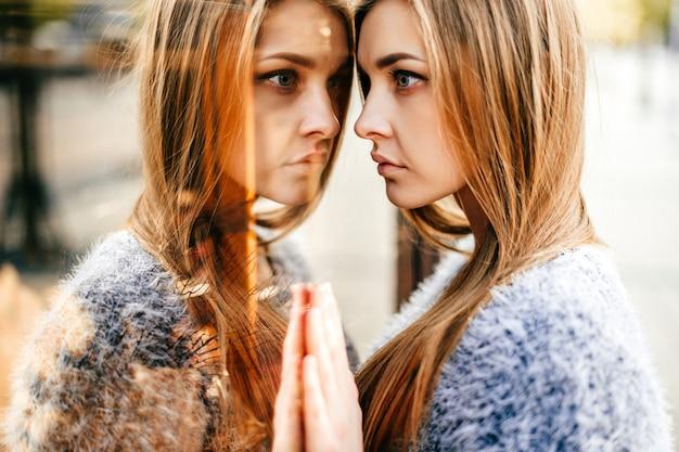 Retrato de uma jovem garota de cabelos longos bonita com rosto emocional, olhando para o reflexo na vitrine espelhada. Foto Premium