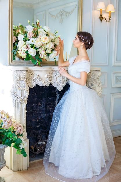 Retrato de uma jovem garota em um lindo vestido no interior, beleza feminina Foto Premium