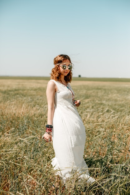 Retrato de uma jovem garota em um vestido branco translúcido no estilo boho ou hippie Foto Premium