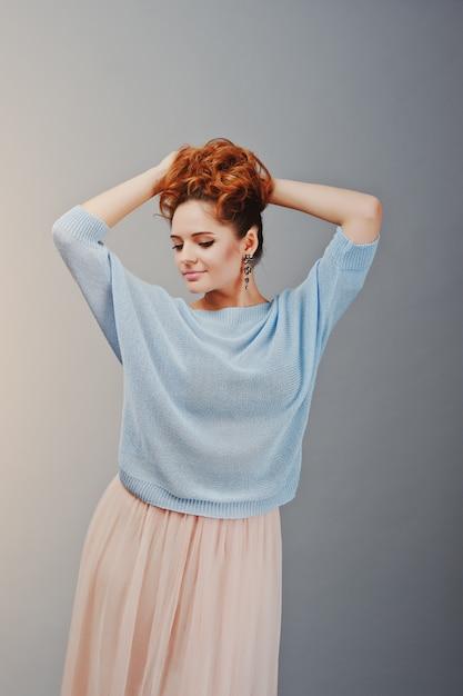Retrato de uma jovem garota encaracolado com cabelo vermelho na blusa azul e saia rosa Foto Premium