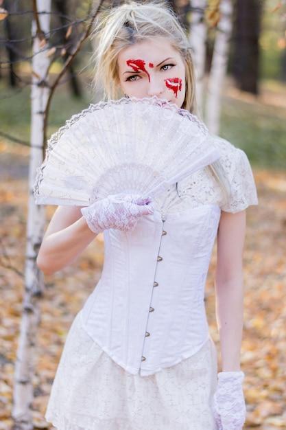 Retrato de uma jovem garota linda com sangue halloween maquiagem no rosto e vestido branco Foto Premium