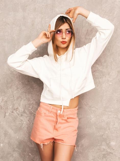 Retrato de uma jovem garota sorridente bonita roupas de esporte na moda verão. mulher despreocupada sexy posando. modelo positivo se divertindo em óculos de sol Foto gratuita