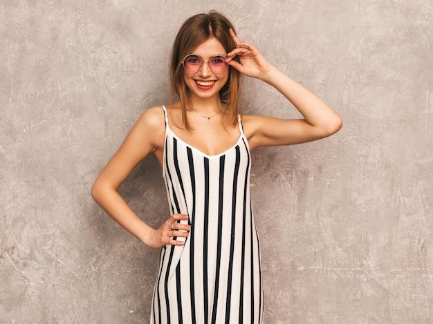 Retrato de uma jovem garota sorridente linda num vestido de zebra na moda verão. mulher despreocupada sexy posando. modelo positivo se divertindo em óculos de sol redondos Foto gratuita